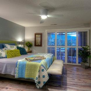 Пример оригинального дизайна: маленькая хозяйская спальня в современном стиле с серыми стенами, пробковым полом и горизонтальным камином