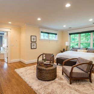 Foto på ett stort funkis huvudsovrum, med gula väggar, mellanmörkt trägolv, brunt golv, en standard öppen spis och en spiselkrans i betong