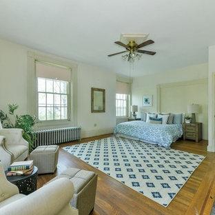Ejemplo de dormitorio principal, clásico, grande, con paredes blancas, suelo de madera en tonos medios, suelo marrón, chimenea tradicional y marco de chimenea de ladrillo