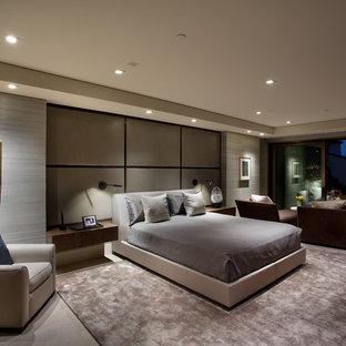 Réalisation d'une très grand chambre parentale minimaliste avec un mur gris, un sol en calcaire et un sol beige.