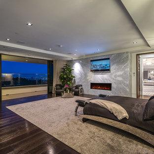 Großes Modernes Gästezimmer mit grauer Wandfarbe, dunklem Holzboden, Hängekamin, Kaminumrandung aus Stein, braunem Boden und eingelassener Decke in Los Angeles