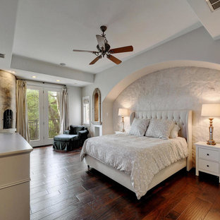 Example of a tuscan dark wood floor bedroom design in Austin with white walls and no fireplace