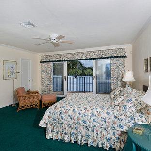 Imagen de dormitorio principal, tropical, de tamaño medio, sin chimenea, con paredes beige, moqueta y suelo verde