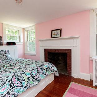 Ispirazione per una camera degli ospiti classica di medie dimensioni con pareti rosa, pavimento in legno massello medio, pavimento beige, camino classico e cornice del camino in legno