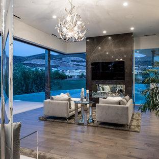 ラスベガスの広いコンテンポラリースタイルのおしゃれな主寝室 (マルチカラーの壁、濃色無垢フローリング、茶色い床、横長型暖炉、石材の暖炉まわり)