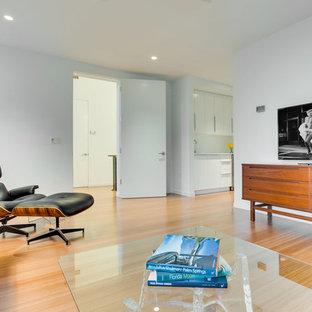 Imagen de dormitorio tipo loft, actual, grande, con paredes blancas y suelo de bambú