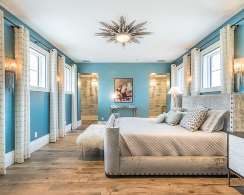 Inspiration for a tropical light wood floor bedroom remodel in Miami with  blue walls