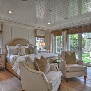 Esempio di una camera da letto costiera con pareti bianche e parquet chiaro