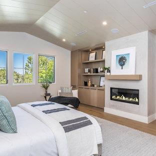 Modelo de dormitorio principal, de estilo de casa de campo, grande, con paredes beige, suelo de madera clara, chimenea lineal, marco de chimenea de hormigón y suelo beige