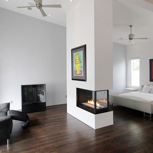 Photo of a contemporary master bedroom in Houston with a two-sided fireplace, white walls and dark hardwood flooring.