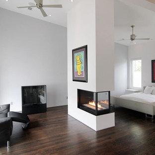 Modern inredning av ett huvudsovrum, med en dubbelsidig öppen spis, vita väggar och mörkt trägolv