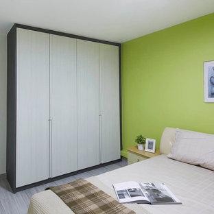 Ispirazione per una camera matrimoniale minimal di medie dimensioni con pareti verdi e pavimento in compensato