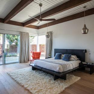 Midcentury modern master medium tone wood floor and beige floor bedroom photo in Orange County with white walls