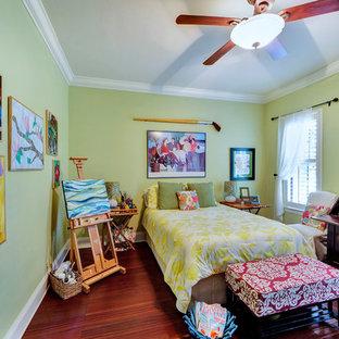 Modelo de dormitorio principal, tradicional, sin chimenea, con paredes verdes, suelo de madera oscura y suelo rojo