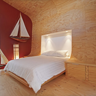 Photo of a small contemporary loft-style bedroom in Adelaide with multi-coloured walls and plywood floors.