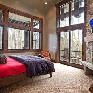 Exemple d'une chambre avec moquette montagne avec un mur beige, une cheminée d'angle et un manteau de cheminée en pierre.