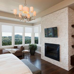 ポートランドの広いコンテンポラリースタイルのおしゃれな主寝室 (ベージュの壁、濃色無垢フローリング、標準型暖炉、石材の暖炉まわり、茶色い床) のインテリア