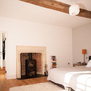 オックスフォードシャーの広いカントリー風おしゃれな主寝室 (白い壁、淡色無垢フローリング、薪ストーブ、石材の暖炉まわり) のインテリア