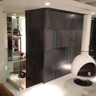Ejemplo de dormitorio moderno con suelo de cemento, estufa de leña y marco de chimenea de metal