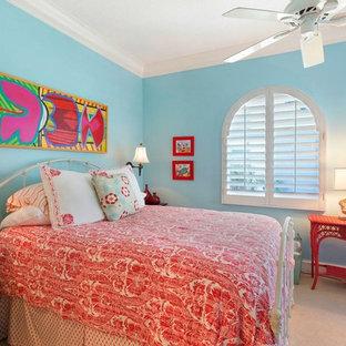 Diseño de dormitorio principal, costero, de tamaño medio, con paredes azules, moqueta, chimenea de esquina, marco de chimenea de hormigón y suelo beige