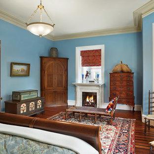 Идея дизайна: большая хозяйская спальня в викторианском стиле с синими стенами, темным паркетным полом, стандартным камином и фасадом камина из штукатурки