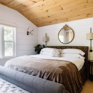Kleines Landhaus Hauptschlafzimmer mit weißer Wandfarbe, hellem Holzboden, Kaminofen und weißem Boden in New York