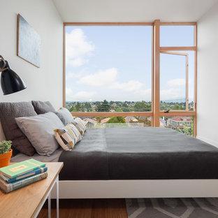 Diseño de dormitorio actual, pequeño, con suelo de bambú y paredes blancas