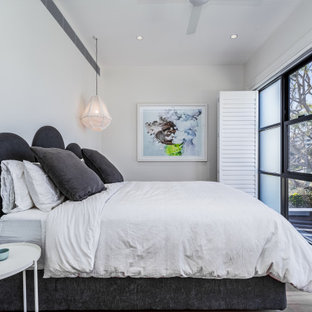 Design ideas for a contemporary bedroom in Sydney with white walls, dark hardwood floors and brown floor.