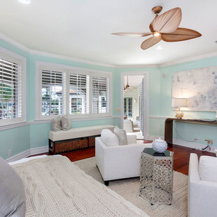 Mid-sized tuscan master medium tone wood floor and red floor bedroom photo in Miami with green walls and no fireplace