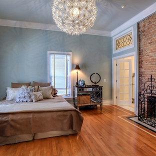 Ejemplo de dormitorio principal, clásico, de tamaño medio, con paredes azules, suelo de madera en tonos medios, chimenea tradicional y marco de chimenea de ladrillo