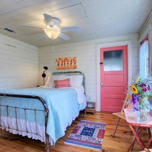Kleines Shabby-Style Schlafzimmer mit weißer Wandfarbe, braunem Holzboden, braunem Boden, Holzdielendecke und Holzdielenwänden in Little Rock