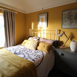 Ejemplo de habitación de invitados escandinava, pequeña, con paredes amarillas, suelo de madera oscura, chimenea tradicional y marco de chimenea de baldosas y/o azulejos