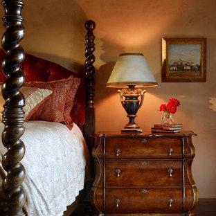Ispirazione per una camera matrimoniale tradizionale di medie dimensioni con pareti beige, pavimento in legno massello medio e nessun camino