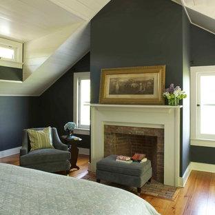 Inspiration för ett lantligt sovrum, med en spiselkrans i tegelsten, grå väggar, mellanmörkt trägolv och en standard öppen spis