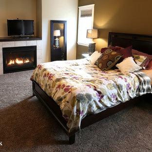 Imagen de dormitorio principal, tradicional renovado, con paredes beige, suelo de cemento, estufa de leña y marco de chimenea de baldosas y/o azulejos