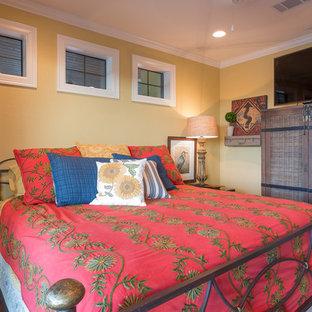 Modelo de dormitorio principal, mediterráneo, de tamaño medio, con paredes amarillas, suelo de madera oscura y suelo marrón