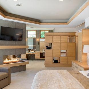 Modelo de dormitorio principal, actual, grande, con paredes blancas, suelo de baldosas de porcelana, marco de chimenea de baldosas y/o azulejos y chimenea de doble cara