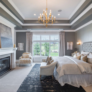 Example of a large transitional master carpeted and beige floor bedroom design in Salt Lake City with gray walls, a standard fireplace and a wood fireplace surround