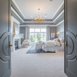 ソルトレイクシティの広いトランジショナルスタイルのおしゃれな主寝室 (グレーの壁、カーペット敷き、標準型暖炉、木材の暖炉まわり) のインテリア