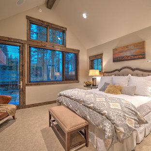 Modelo de dormitorio principal, rural, con paredes beige, moqueta, chimenea tradicional y marco de chimenea de piedra