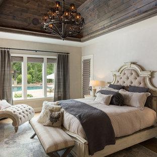 Example of an ornate medium tone wood floor and brown floor bedroom design in Birmingham with beige walls