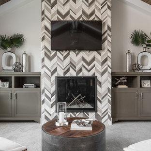 Esempio di una grande camera matrimoniale chic con pareti beige, moquette, camino classico, cornice del camino piastrellata e pavimento grigio