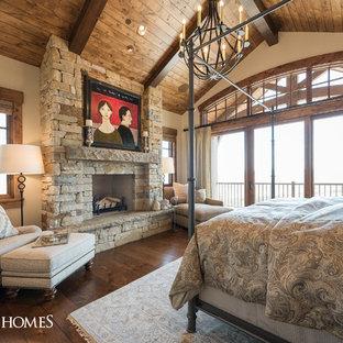 Diseño de dormitorio principal, rural, grande, con paredes blancas, suelo de madera en tonos medios, chimenea tradicional y marco de chimenea de piedra