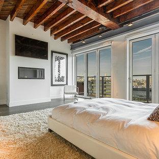 Ejemplo de habitación de invitados urbana con paredes blancas, suelo de madera en tonos medios, chimenea lineal, marco de chimenea de metal y suelo marrón