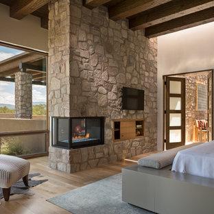 アルバカーキの大きいサンタフェスタイルのおしゃれな主寝室 (ベージュの壁、コーナー設置型暖炉、石材の暖炉まわり、茶色い床、淡色無垢フローリング)