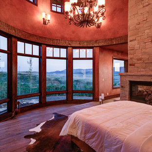 Design ideas for a large country master bedroom in Salt Lake City with red walls, medium hardwood floors, a two-sided fireplace, a stone fireplace surround and brown floor.