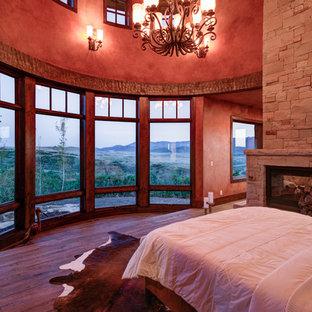 Diseño de dormitorio principal, rústico, grande, con paredes rojas, suelo de madera en tonos medios, chimenea de doble cara, marco de chimenea de piedra y suelo marrón