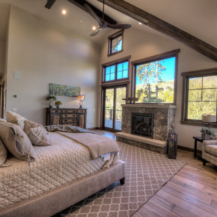 Modelo de dormitorio principal, tradicional renovado, grande, con suelo de madera en tonos medios, chimeneas suspendidas y marco de chimenea de piedra