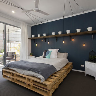 Photo of an industrial bedroom in Sunshine Coast with blue walls, carpet and grey floor.