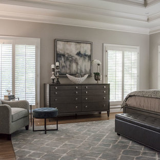 Modelo de dormitorio principal, tradicional renovado, grande, sin chimenea, con paredes grises, suelo de madera en tonos medios y suelo naranja